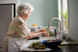 Older lady washing carrots at her kitchen sink.