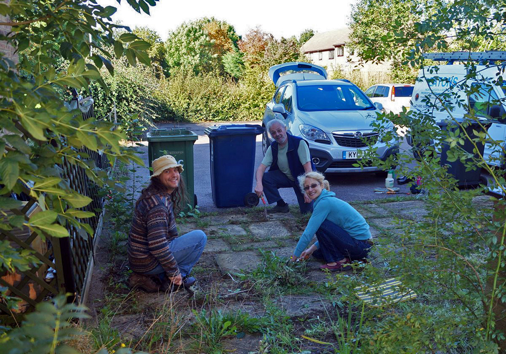 Members of the St Neots timebanking  at work clearing weeds from a patio.
