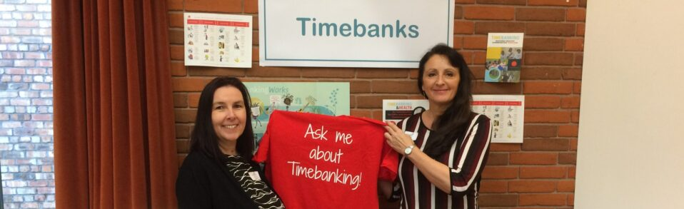 Two women are holding a t shirt that says 'ask me about timebanking'. They are in front of a timebanking display. They're both smiling.