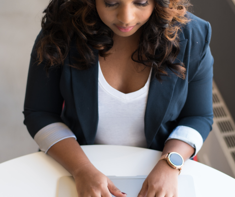 A young black woman with curly hair is working on a laptop.